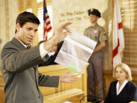 Side profile of a lawyer holding a piece of evidence